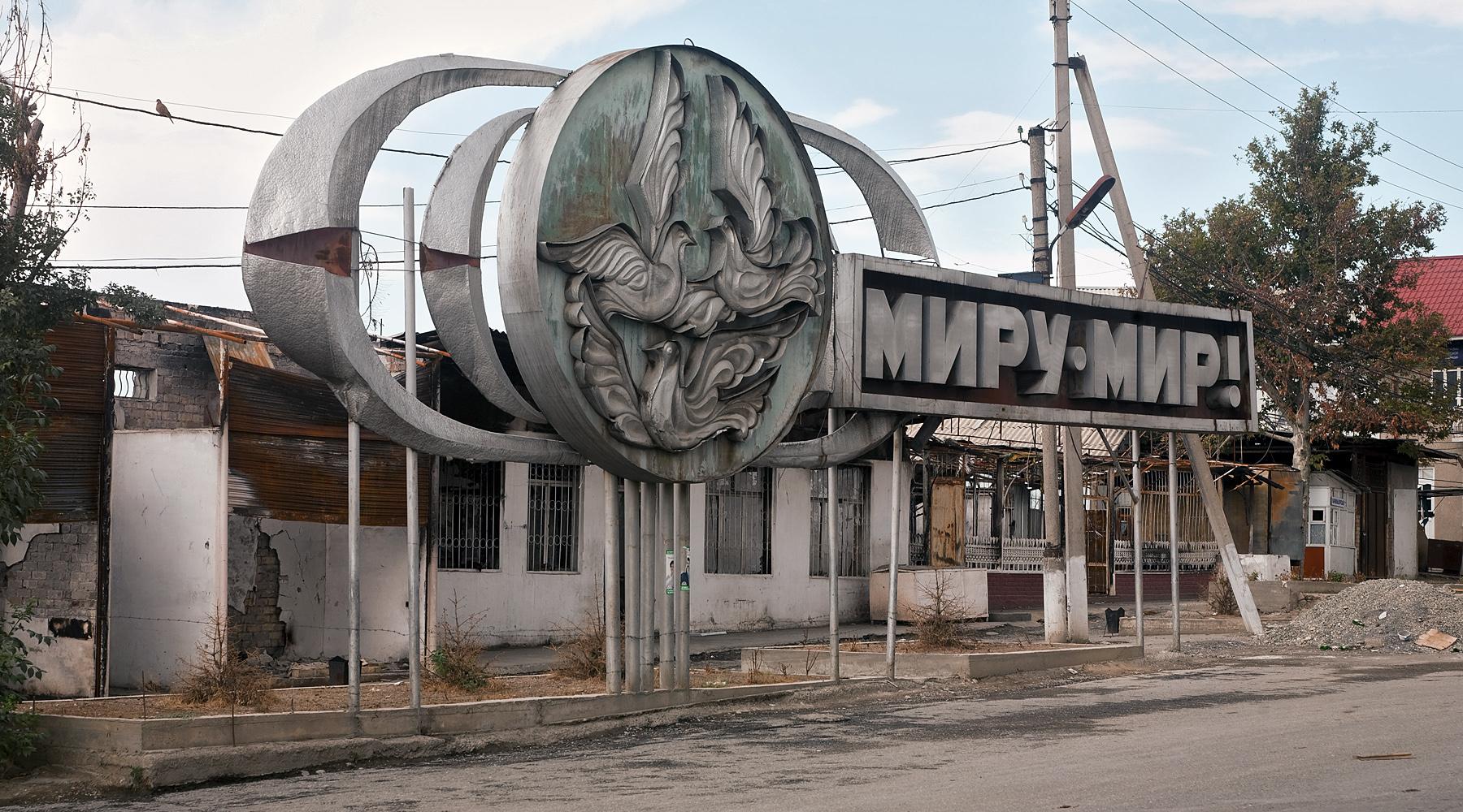 """sowjetische Installation mit der Aufschrift """"Frieden der Welt"""" vor ausgebrannten Gebäuden des Basars in Osch"""